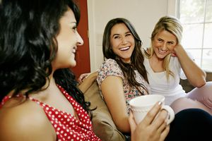 Women having coffee together on sofa