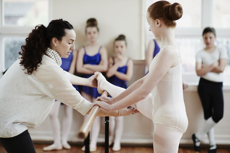 Ballet teacher helping dancer in dance studio