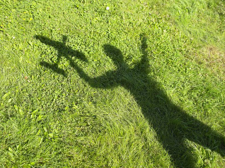 Shadow of a woman holding an rc plane