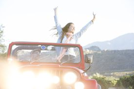 Woman cheering in sport utility vehicle