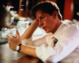 Man sitting at bar looking at glass of liquor