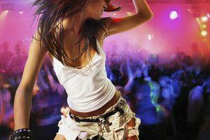 Young female DJ at record decks in nightclub, arm raised