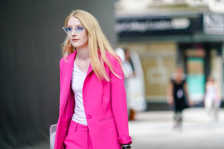 Woman in pink suit and blue sunglasses