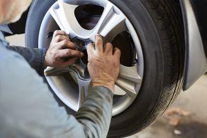 Garage mechanic fitting car wheel