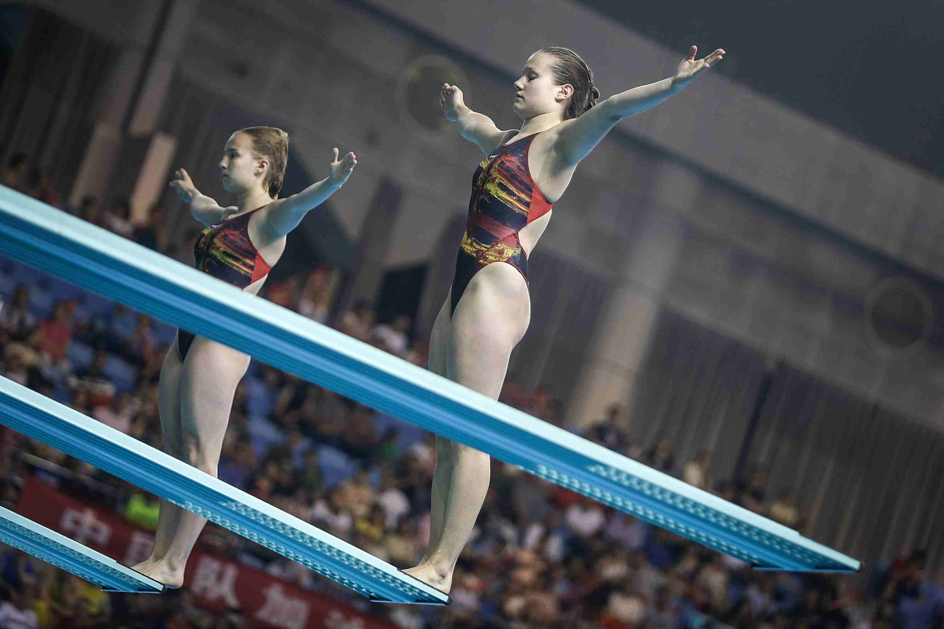 Synchronized divers prepare to perform a reverse dive.