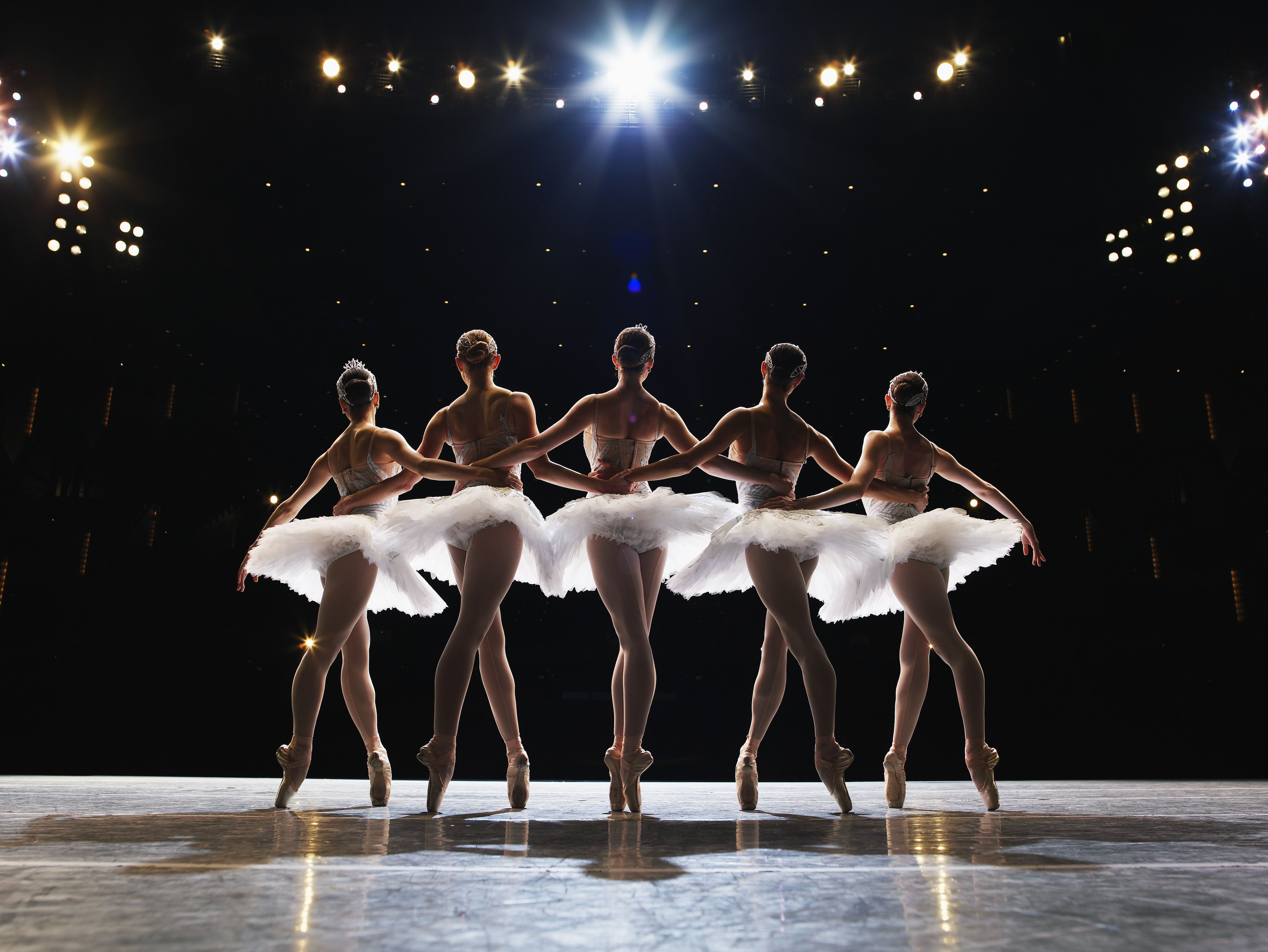 Five ballerinas en pointe on stage, arms around each other, rear view