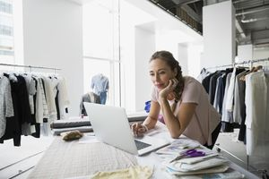 Fashion designer on computer surrounded by clothes