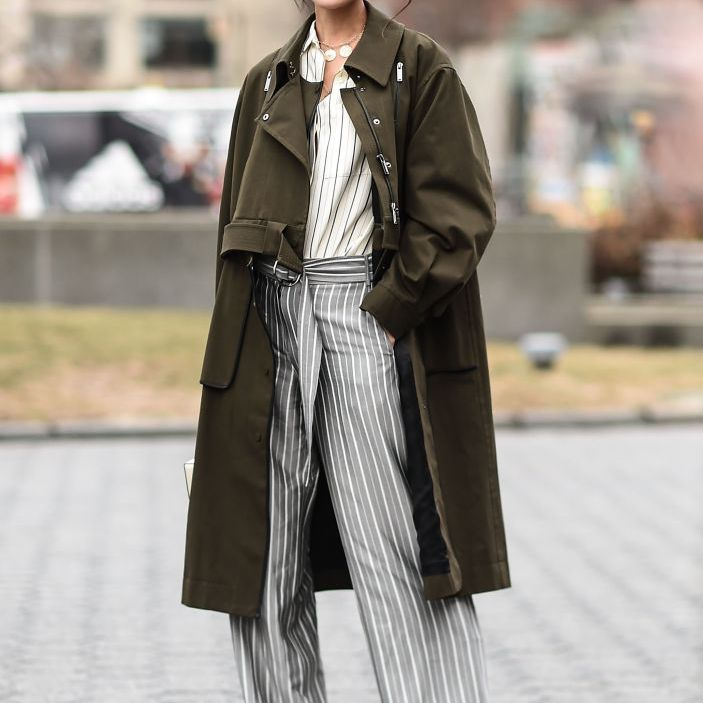 Street style woman in fall outfit with trousers and trench coat