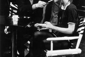 : American Pop artist Andy Warhol (1928 - 1987) sits next to actor Edie Sedgwick