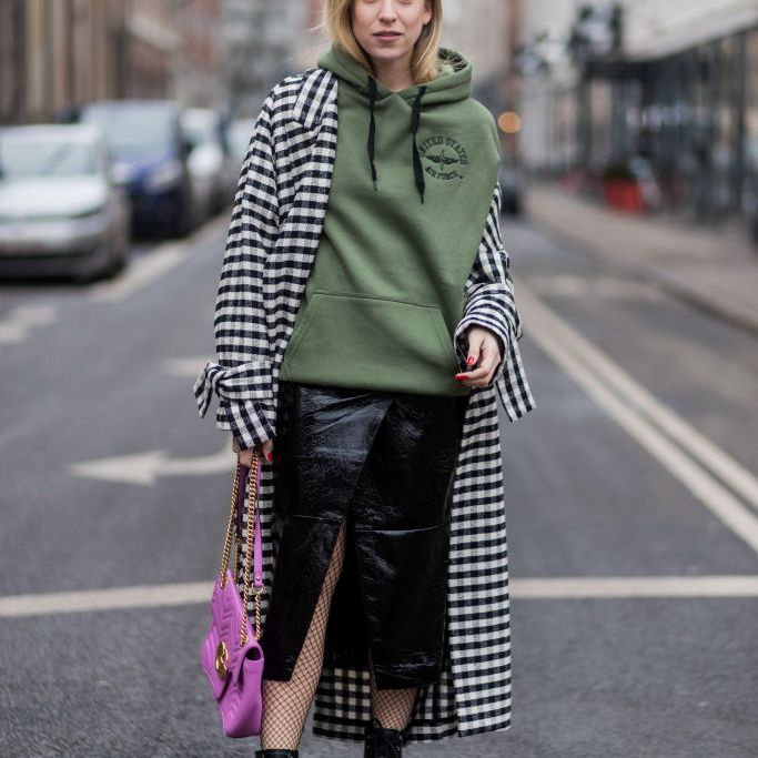 Street style woman in hoodie coat and leather skirt