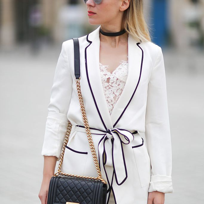 Woman in white blazer with black piping by Zara