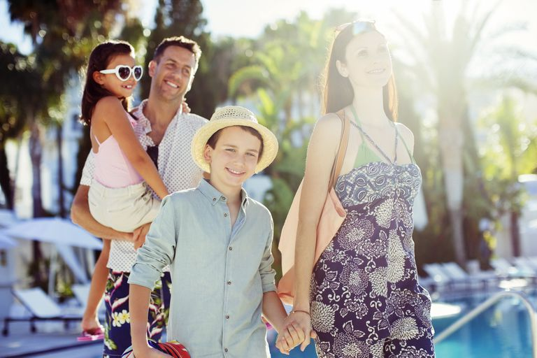 Family with two children walking by resort swimming pool