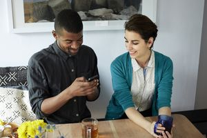 A man uses his cellphone at the table. Can his partner trust him?