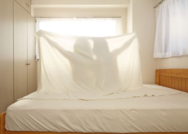 Man and woman under bedsheets