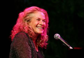 Carole King sitting behind a piano and microphone while performing on stage.