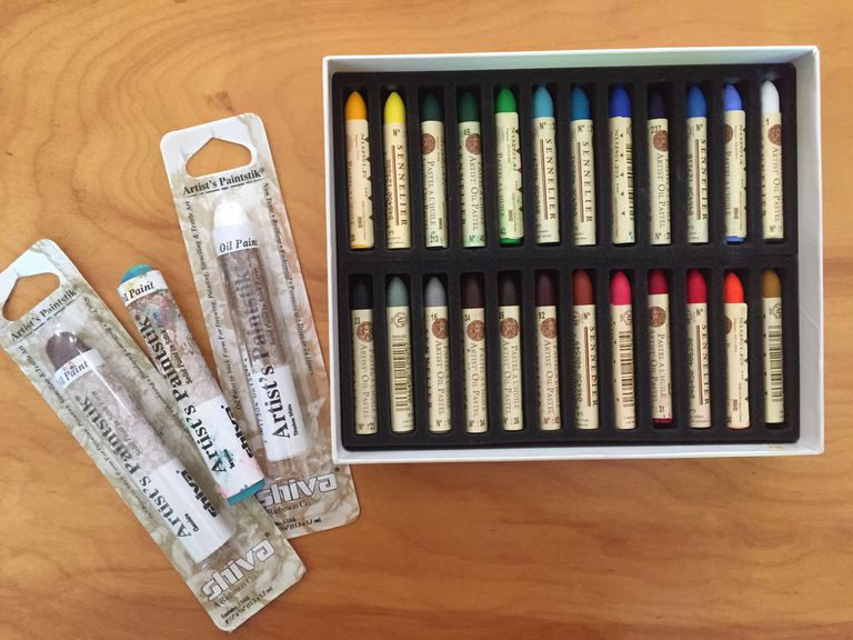 Box of oil pastels and several oil paintsticks