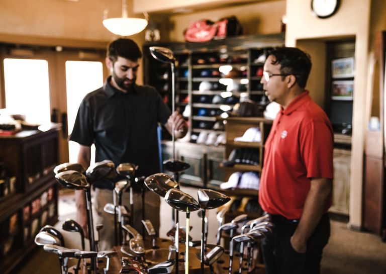 Customer and salesperson in a golf pro shop discussing clubs.