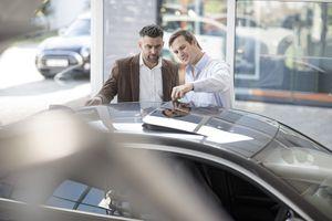 salesman explaining sunroof function on new car