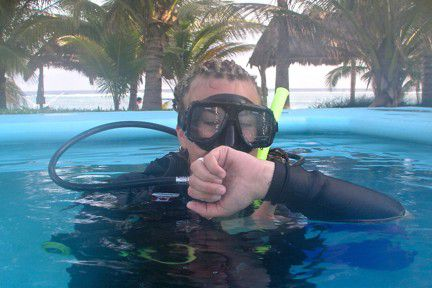 Natalie Novak in scuba gear above the surface checking the time