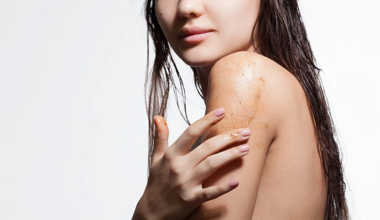 Woman applying body scrub to shoulder