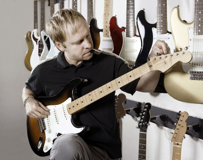 Man tuning guitar.
