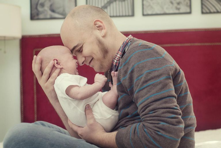 Man holding forehead against newborn son