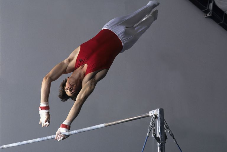 Male gymnast performing on the high bar
