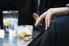 Man's hand on knee holding smoking cigar, close-up