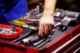 Man Grabbing a Tool From His Toolbox.