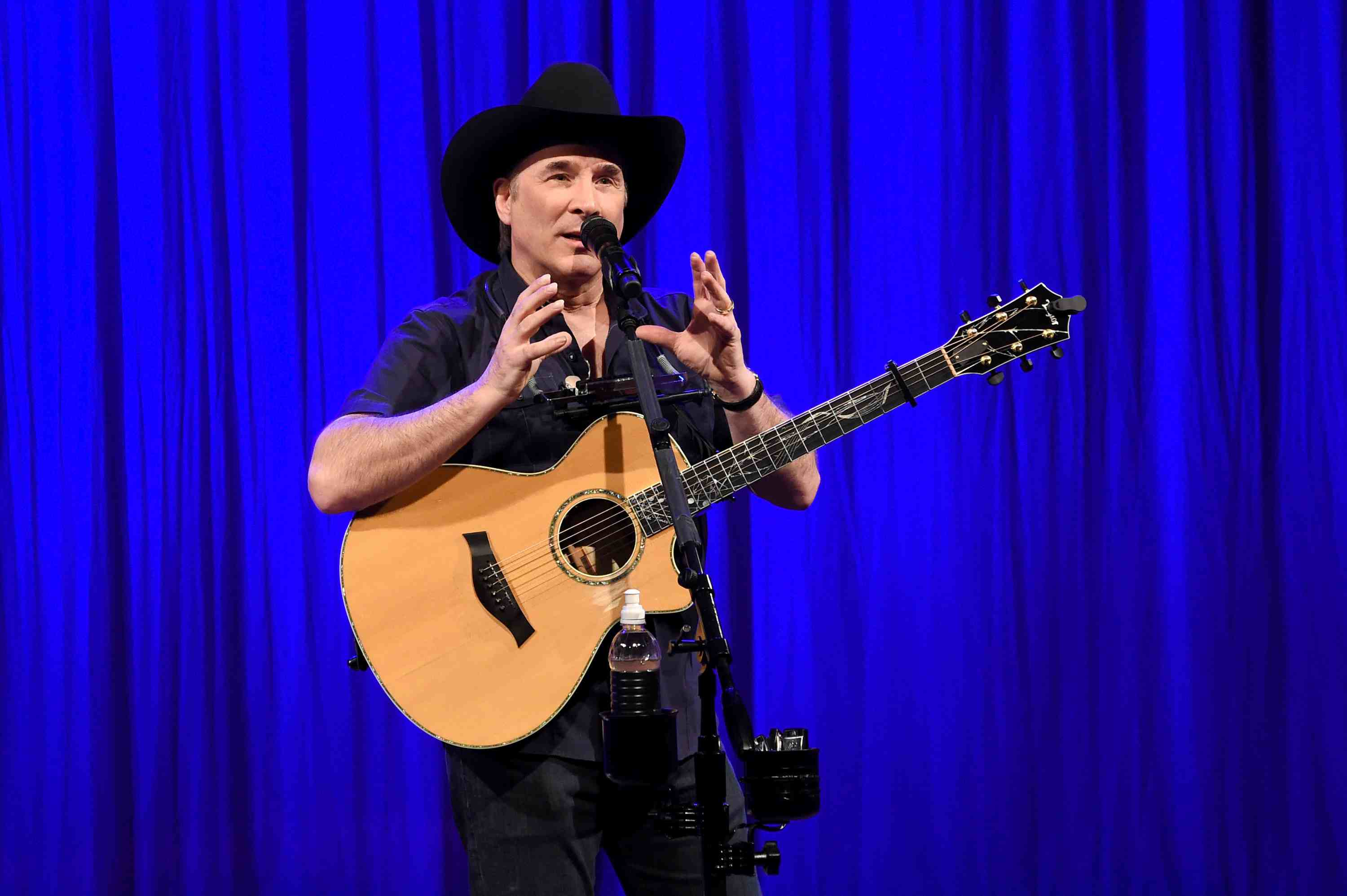 Clint Black performing in front of a blue stage curtain.