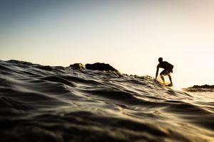 USA, California, Los Angeles County, Malibu, Surfer at sunset