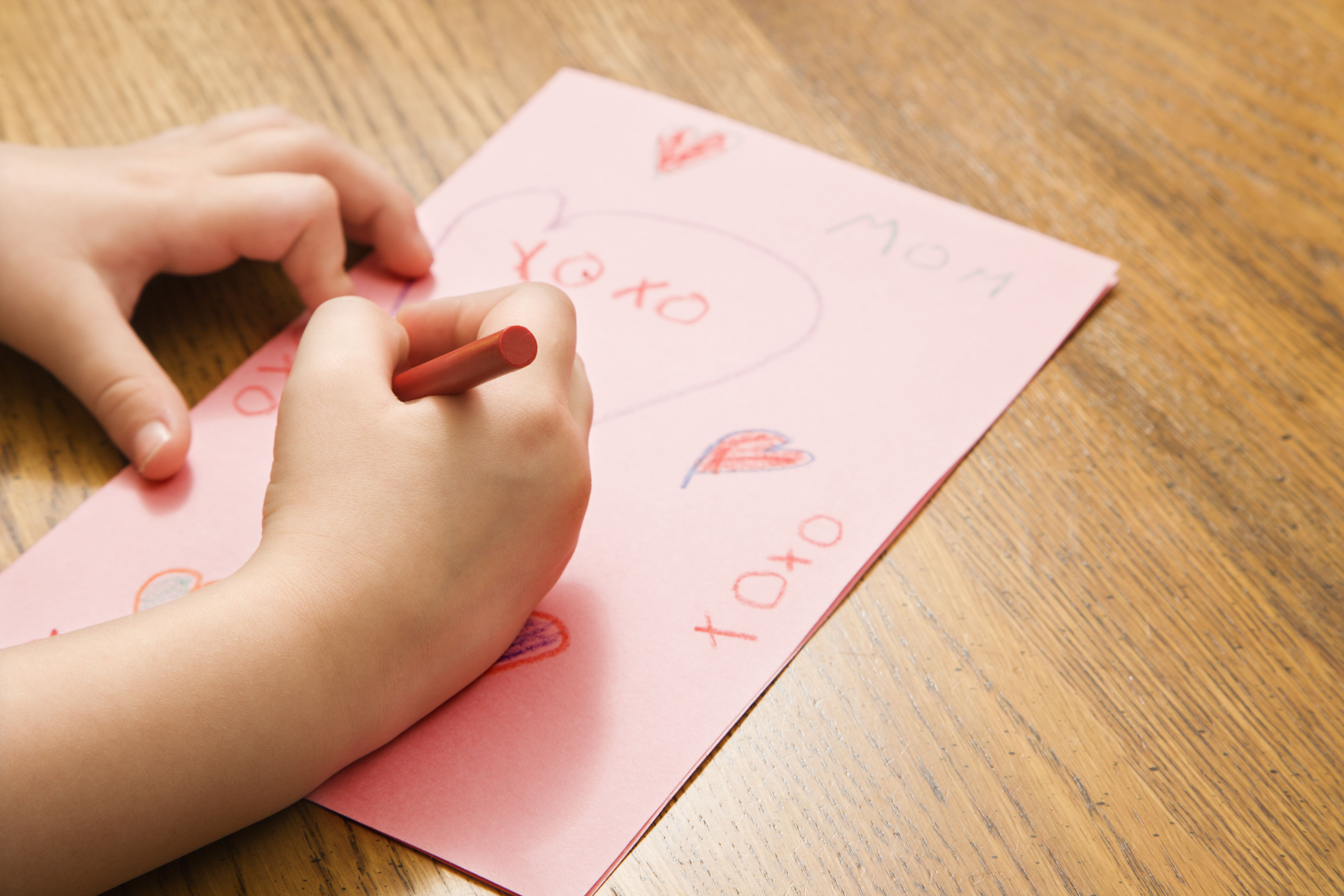 Child hands drawing on paper with crayons