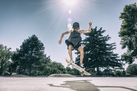 Young woman doing an ollie at skatepark