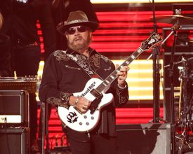 Hank Williams, Jr. playing a guitar in a performance