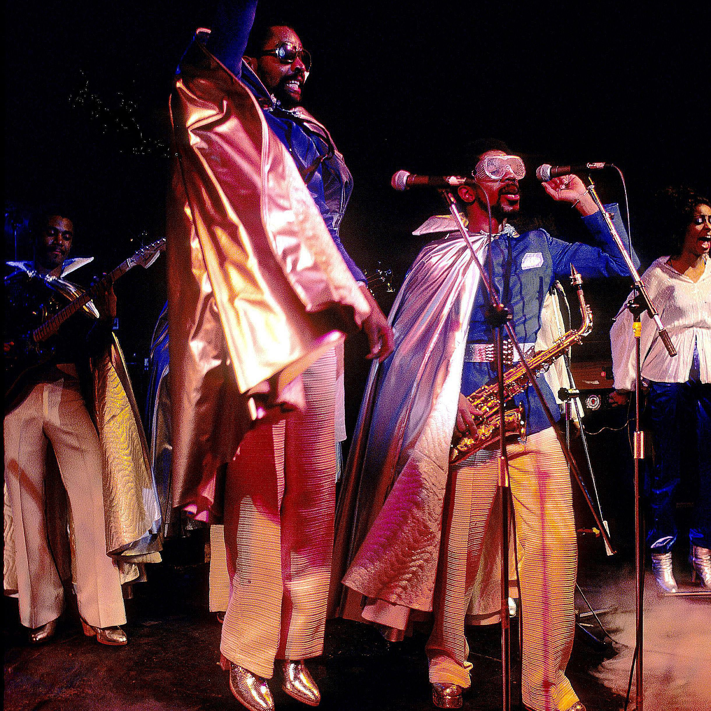 Kool and the Gang singing and dancing on stage.