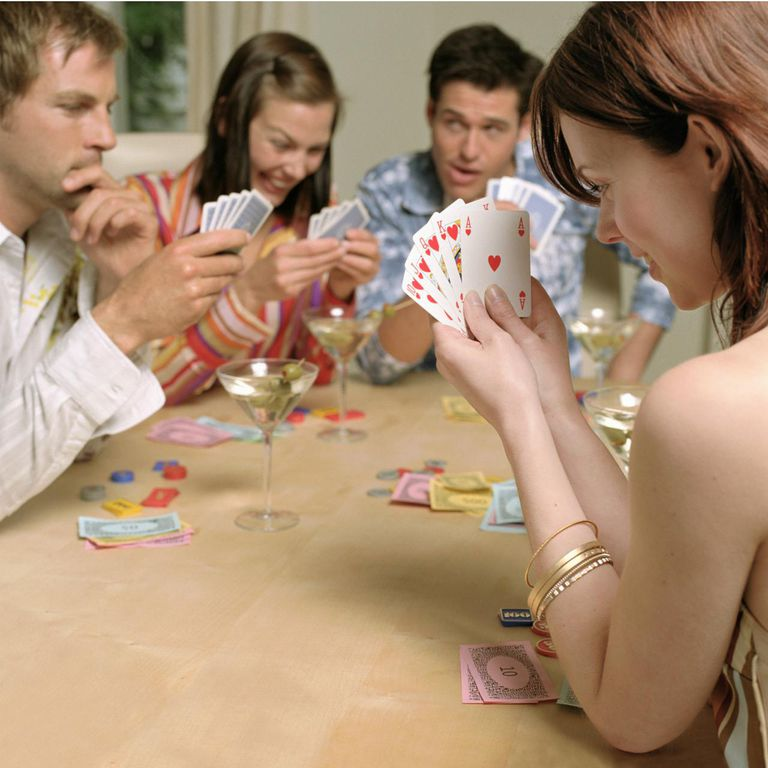 Four people playing poker (focus on woman in foreground)