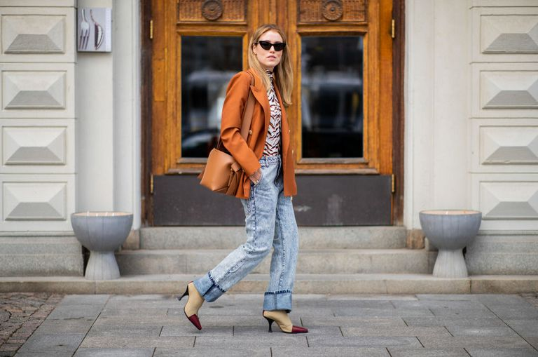 d426764873941 Street style woman in straight leg jeans and orange jacket