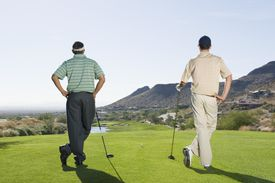Two golfers on the tee waiting to hit drives