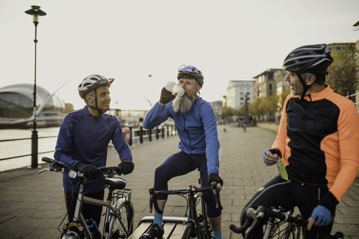 Three cyclists stop for a drink.