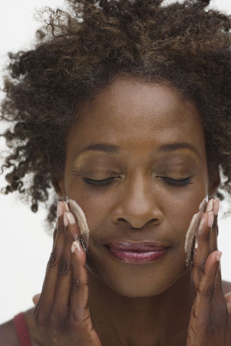 An African American woman putting lotion onto her face.