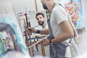 Male artists painting in art class studio