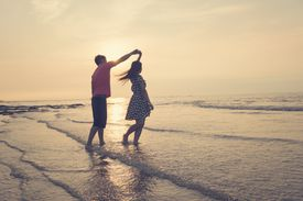 Young couple dancing on beach at sunset.