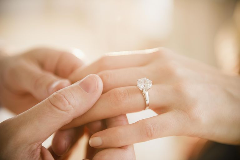 Close up of man and woman's hands with engagement ring