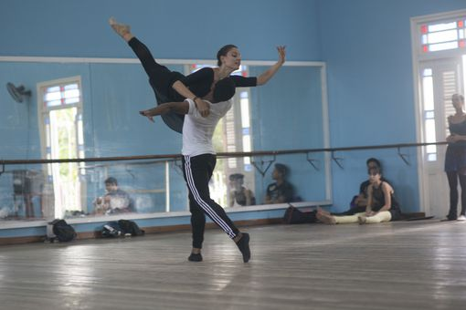 Two people dancing ballet with onlookers