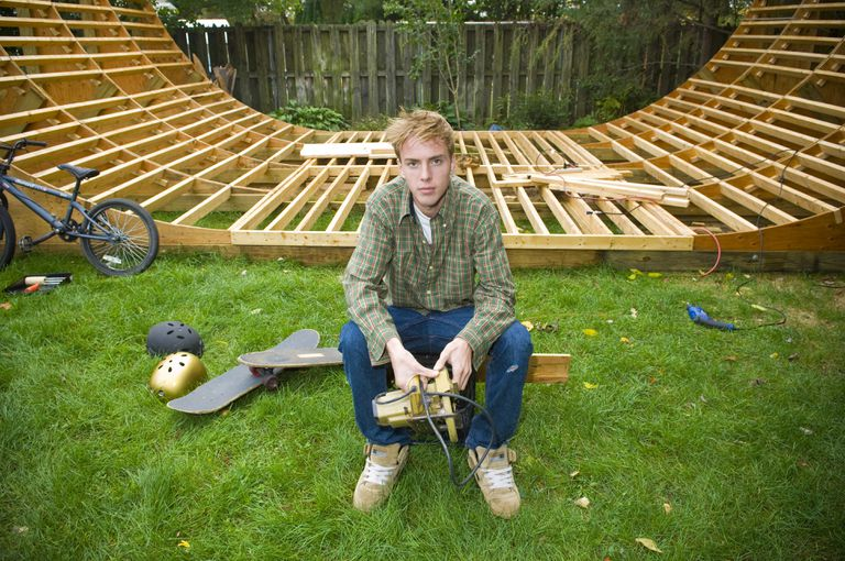 Young man holding circular saw in front of skateboarding ramp frame.