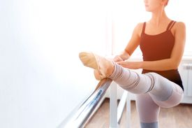 A dancer places her foot on the ballet barre to stretch her hamstrings