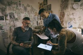 Tattoo artists brainstorming and sketching with digital tablet in tattoo studio office