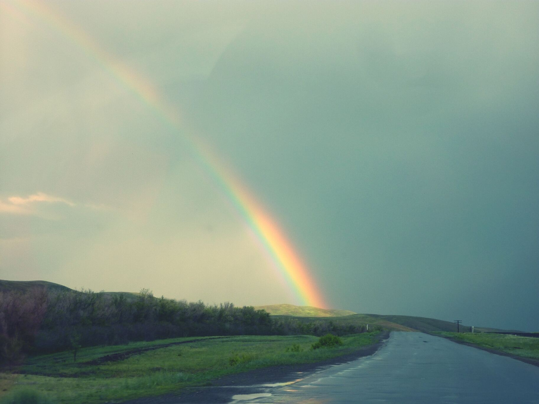 Scenic View Of Rainbow Over Road And Grassy Field