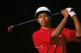 Tiger Woods watches the flight of the ball as he follows through on his swing during a golf tournament in 1992