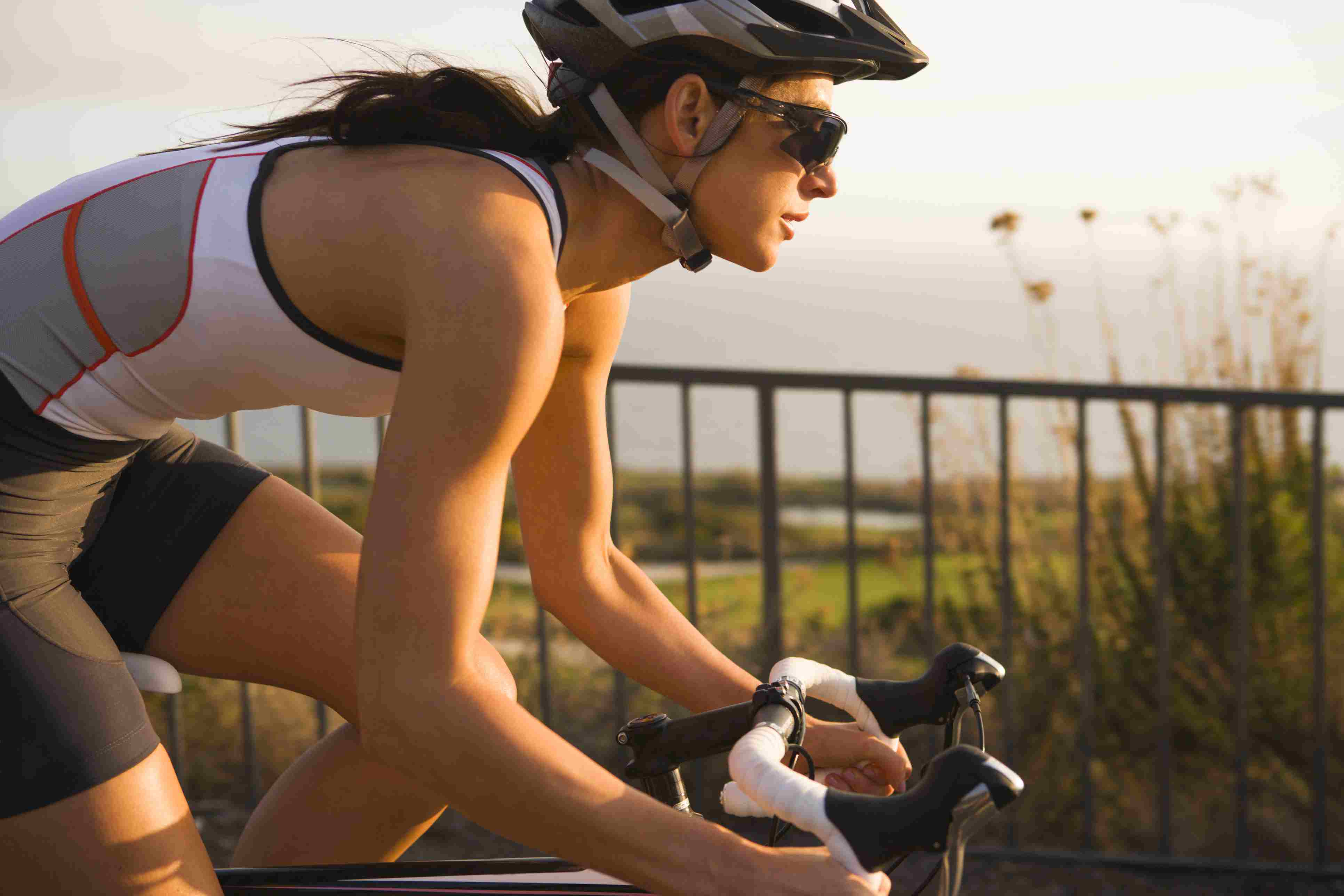A female tri-athlete pedals along a road overlooking the Pacific Ocean in Palos Verdes, California.